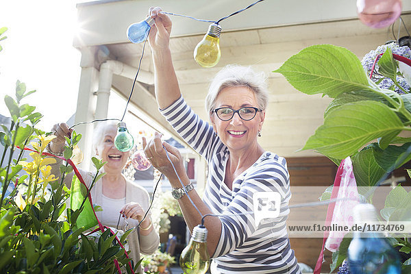 Two women in garden  hanging colourful lights
