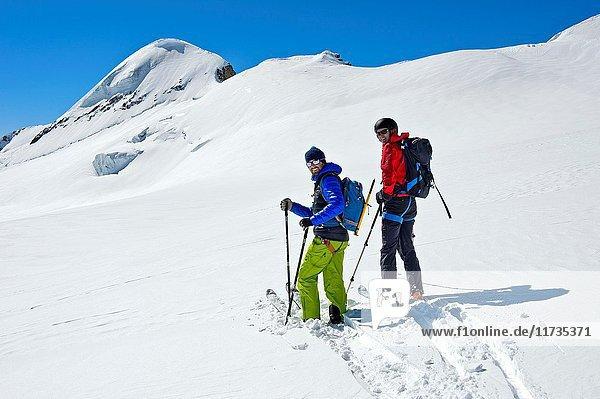 Two skiers on a ski tour on the Aebeni Flue firn fiel beneath the Mittagshorn peak  Loetschental  Valais  Switzerland.