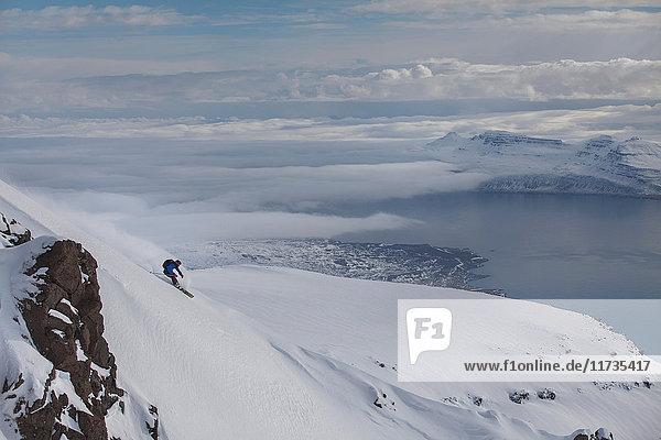 Mann beim Snowboarding am Berg Eskifjordur  Island