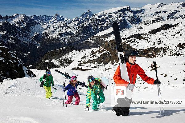 Gruppe von Skifahrern  die mit Skiausrüstung den Berg besteigen