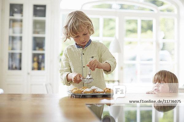 Jungen  die in der Küche Cupcakes backen