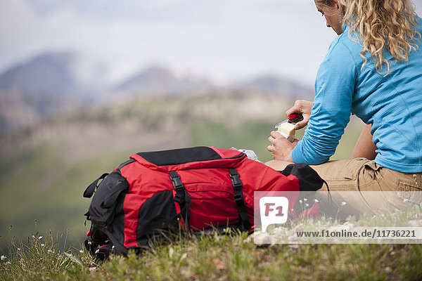 Young woman sitting on grass with red backpack