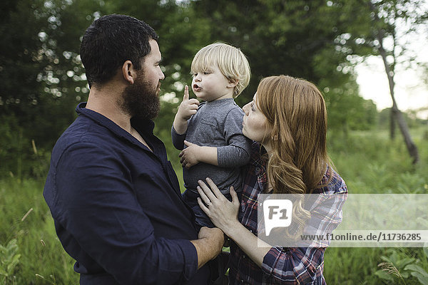 Mother and father holding young son  outdoors