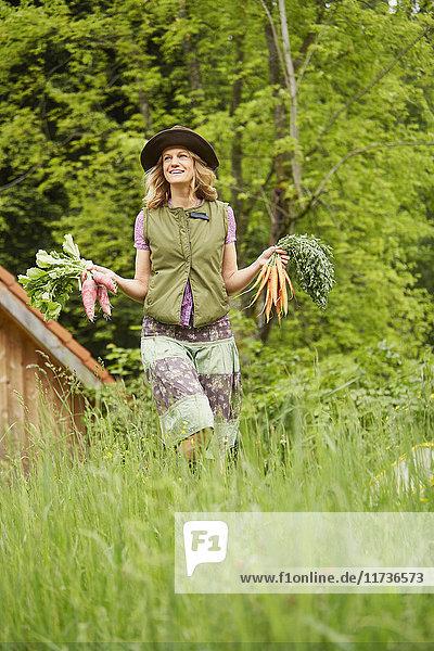 Frau trägt Gemüse auf dem Feld