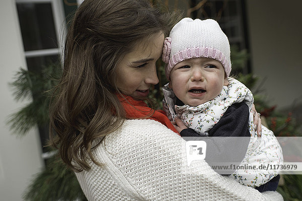 Young girl  crying  being consoled by mother  outdoors