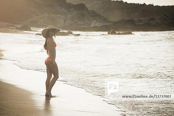 Mittlere erwachsene Frau mit Sonnenhut und Bikini am Strand stehend  Maui  Hawaii  USA