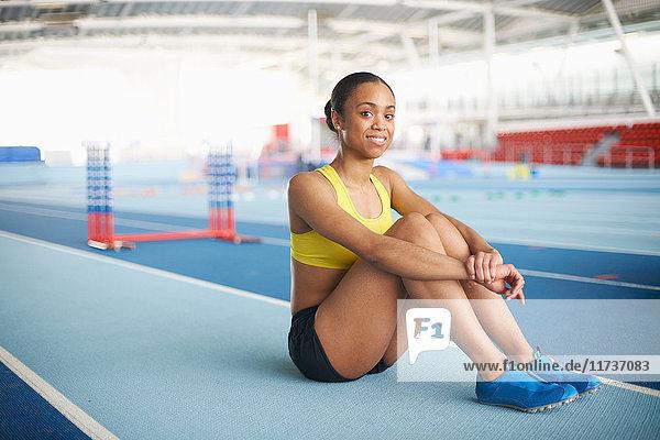 Junge Sportlerin am Boden sitzend  Porträt