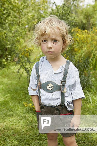 Bildnis eines traurigen Jungen mit zerkratztem Gesicht in Lederhosen Bildnis eines traurigen Jungen mit zerkratztem Gesicht in Lederhosen