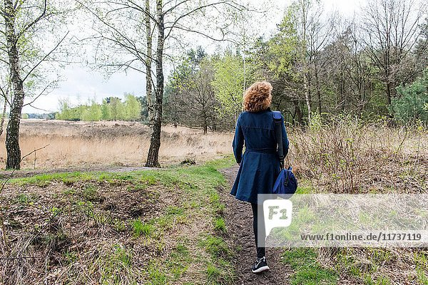Regte Heide  Riel  Netherlands. Red headed caucasian woman strolling a nature reserve park and forest on a free weekend afternoon.