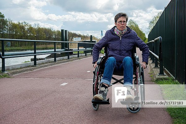 Tilburg  Netherlands. Female multiple sclerosis patient dealing with her condition by on and off using a wheelchair to get along.
