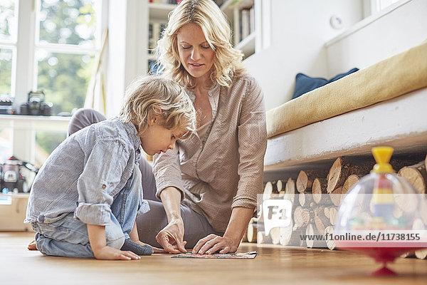 Mutter und Sohn sitzen auf dem Boden und puzzeln zusammen