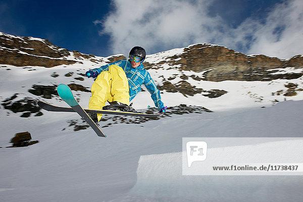 Männlicher Skifahrer in der Luft mit gekreuzten Skiern