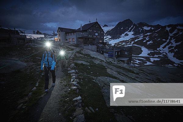 Young couple hiking at night wearing headlamps on path at Val Senales Glacier  Val Senales  South Tyrol  Italy