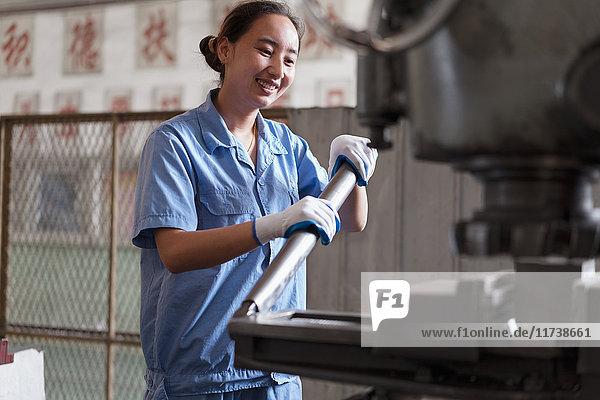 Fabrikarbeiterin schiebt Maschinenhebel in Kranfabrik  China