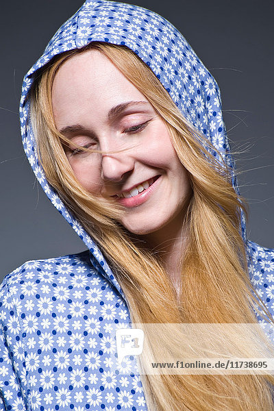 Mid adult woman wearing hood and smiling