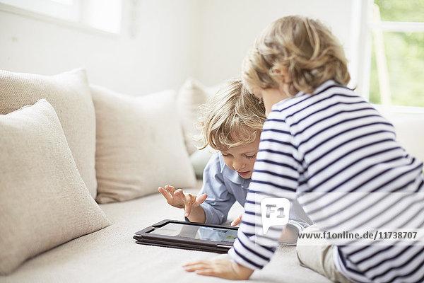 Zwei Jungen sitzen auf dem Sofa und benutzen ein digitales Tablett