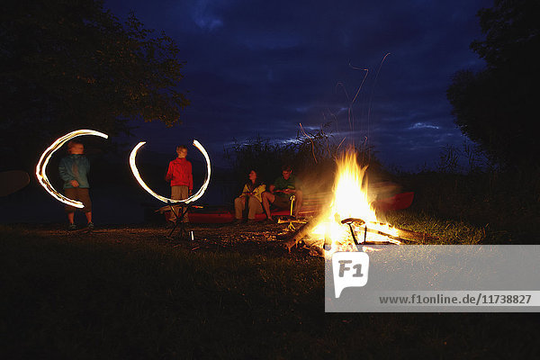 Family by camp fire  children making light trails in the air