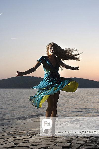Junge Frau dreht sich bei Sonnenuntergang am Wasser herum  Milna  Brac  Kroatien