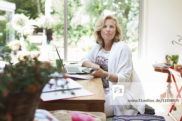 Portrait of mature woman sitting at table  using laptop  holding smartphone