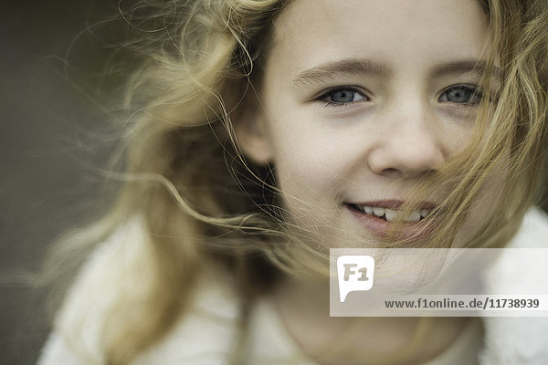 Close up portrait of girl with long blond flyaway hair