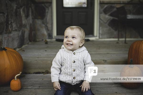 Kleiner Junge sitzt auf der Veranda mit Kürbissen und schaut lächelnd nach oben