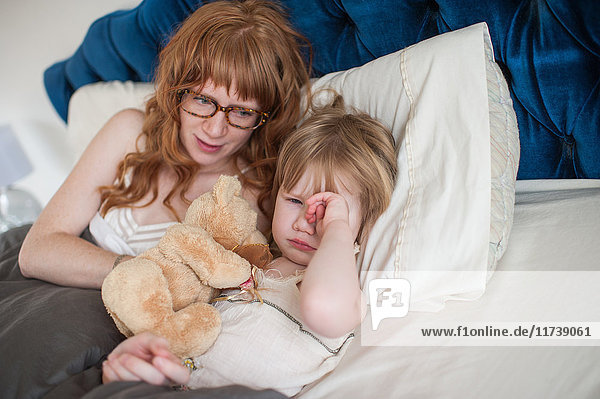 Girl rubbing eyes in bed  mother comforting