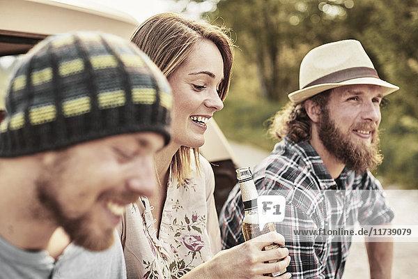 Drei Personen halten Flaschenbier lächelnd in der Hand