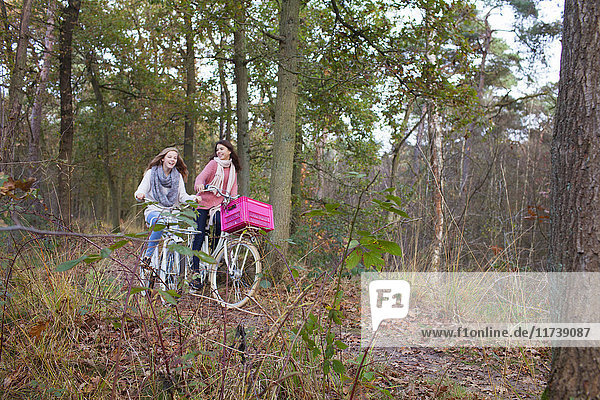 Teenage girls in forest cycling on bicycles with pink crate attached