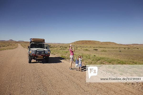 Geländewagen geparkt  während Mutter und Kinder die Aussicht genießen  Sesfontein  Kaokoland  Namibia