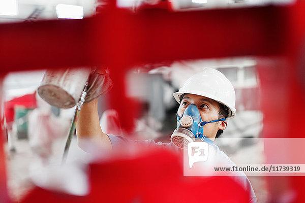 Nahaufnahme eines männlichen Fabrikarbeiters  der einen roten Kran in einer Fabrikhalle besprüht  China