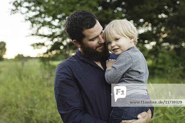 Father holding young son in field
