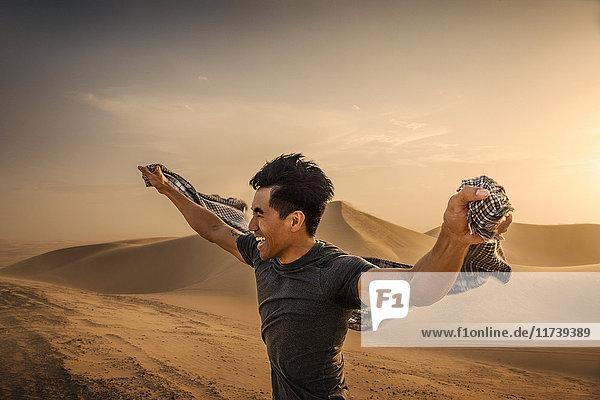 Mann hält Schal im Wind  Glamis-Sanddünen  Kalifornien  USA