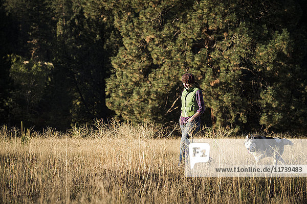 Mid adult woman walking dog in tall grass looking down smiling  Missoula  Montana  USA