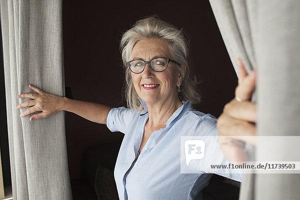 Ältere Frau öffnet Vorhänge und lächelt