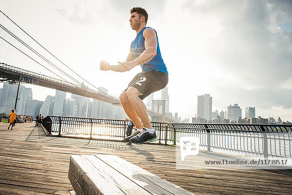 Young man doing jump training on riverside  Brooklyn  New York  USA