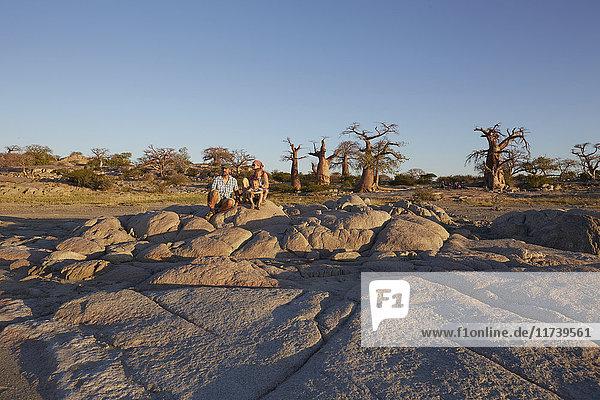 Familie sitzt auf Felsen und schaut auf die Aussicht  Gweta  makgadikgadi  Botswana