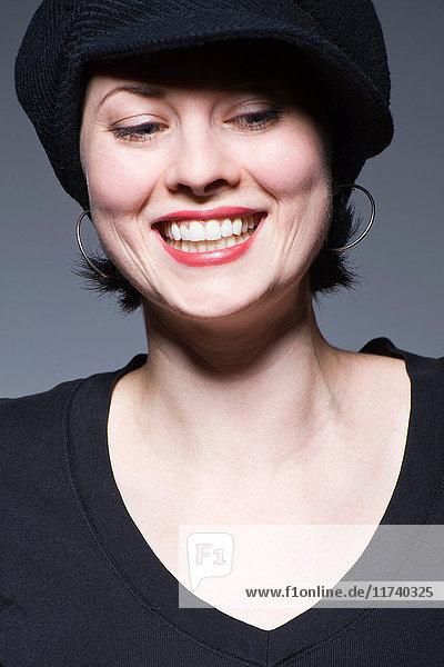 Junge Frau mit schwarzem Hut schaut nach unten und lächelt
