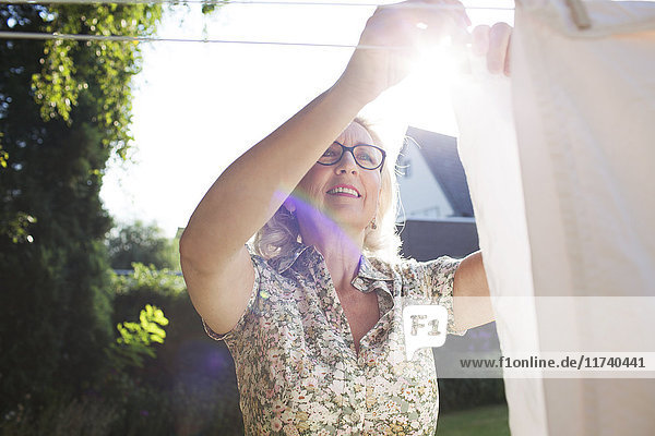 Senior woman hanging out washing in garden
