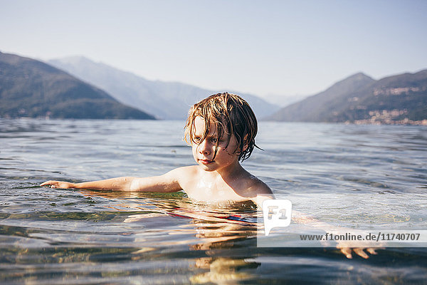 Mountain range and head and shoulders of boy in water arms open looking away  Luino  Lombardy  Italy