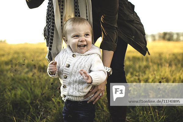 Mid section of mother bending over supporting standing smiling baby boy