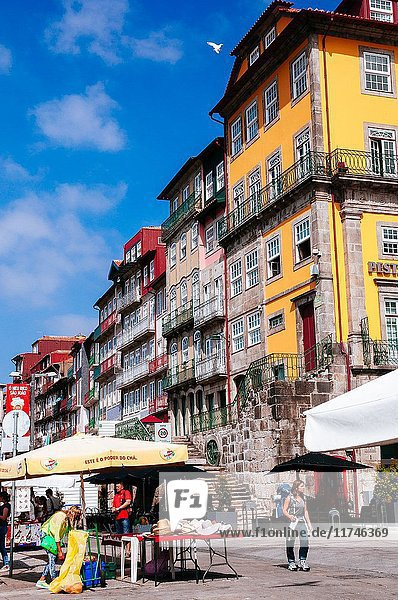 Market street stalls in front of beautiful old buildings  Porto  Portugal.