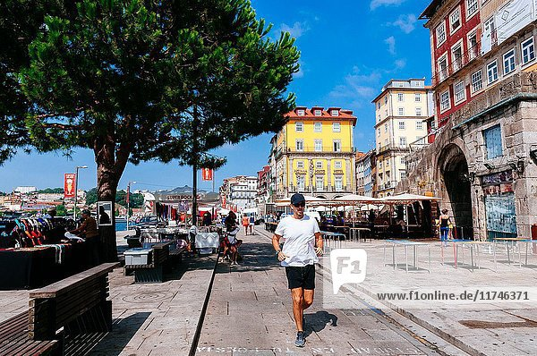 Man running among market street stalls and colouful old buildings  Porto  Portugal.