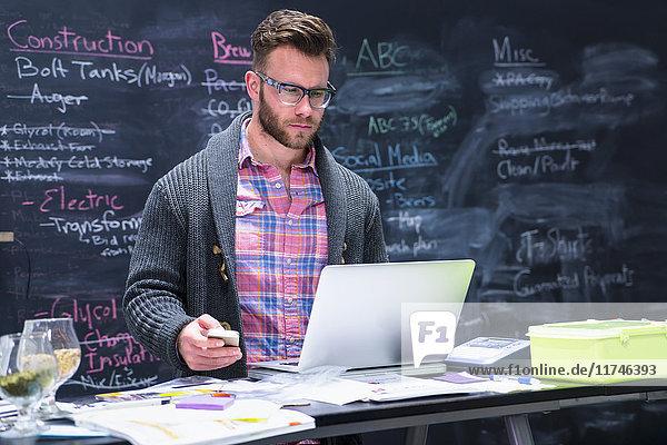 Junger Mann am Arbeitsplatz mit Laptop und Smartphone in der Hand