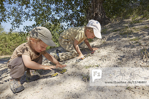 Two young boys  playing with toy cars on sand