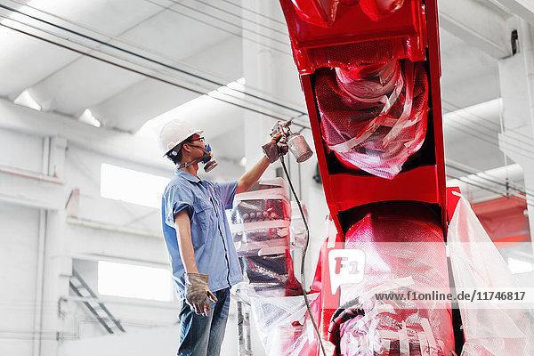 Männlicher Fabrikarbeiter besprüht einen roten Kran in einer Fabrik  China