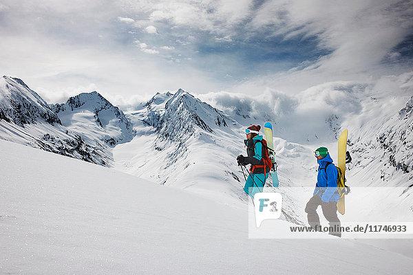 Junge Leute klettern mit Skiausrüstung auf den Gipfel eines Berges