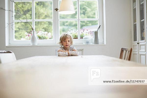 Porträt eines Jungen  der an einem leeren Esstisch sitzt