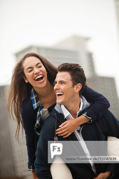 Young man carrying woman on piggyback  laughing