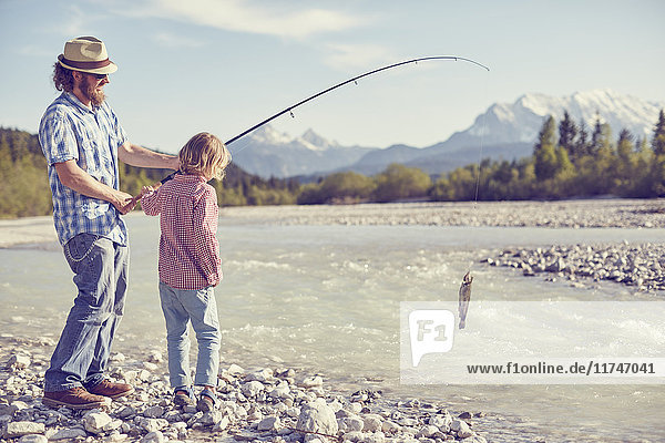 Mid adult man and boy near river holding fishing rod with fish attached  Wallgau  Bavaria  Germany