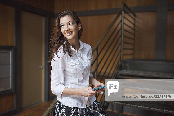 Young woman standing by metal staircase  holding digital tablet